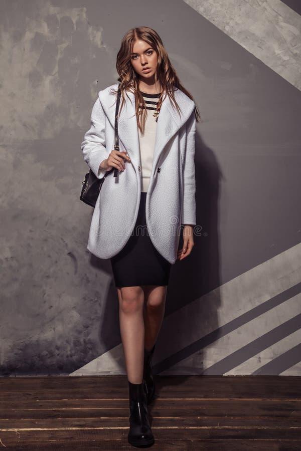 Портрет девушки фотомодели полнометражный в белом пальто высоко стоковая фотография rf