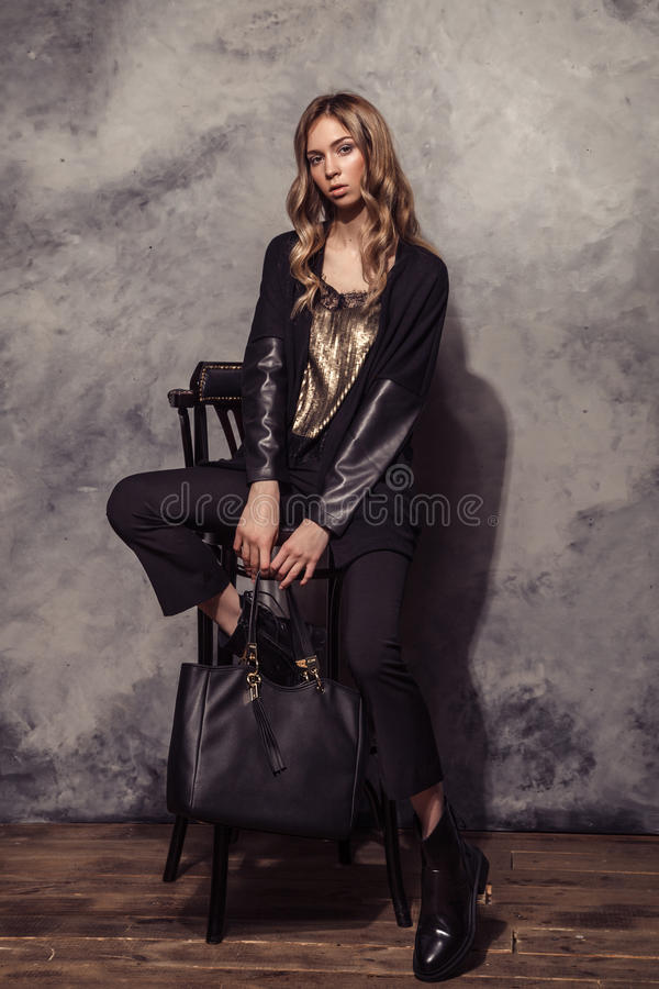 Портрет девушки фотомодели полнометражный в черном костюме высоко стоковое изображение