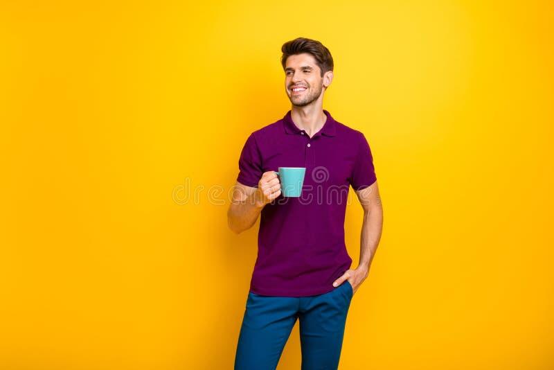 Портрет его привлекательного веселого парня, пьющего эспрессо, изолированного из-за яркого яркого блеска стоковые изображения