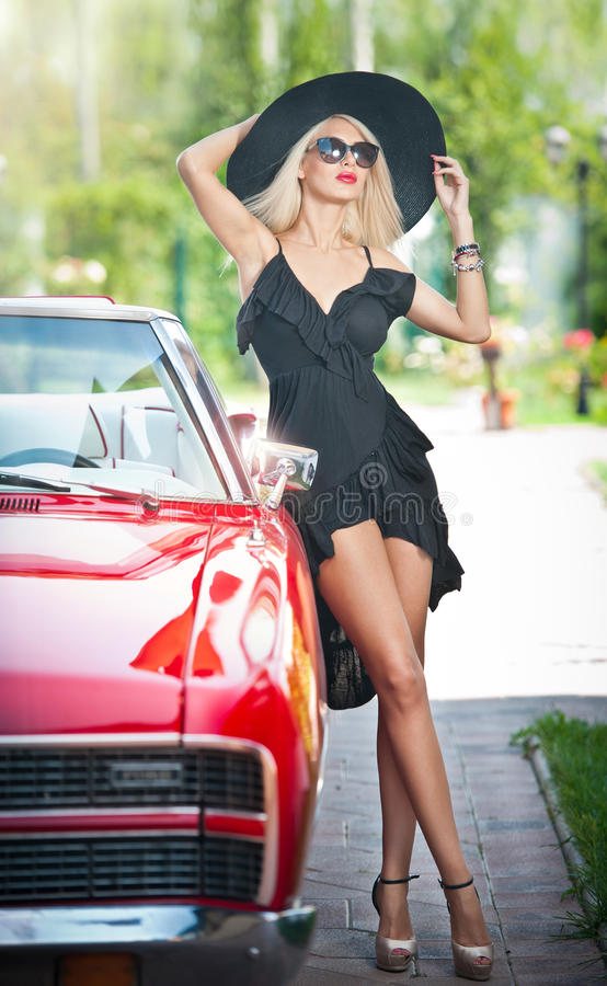 Портрет лета стильной белокурой винтажной женщины при длинные ноги представляя около красного ретро автомобиля модная привлекател стоковые фотографии rf