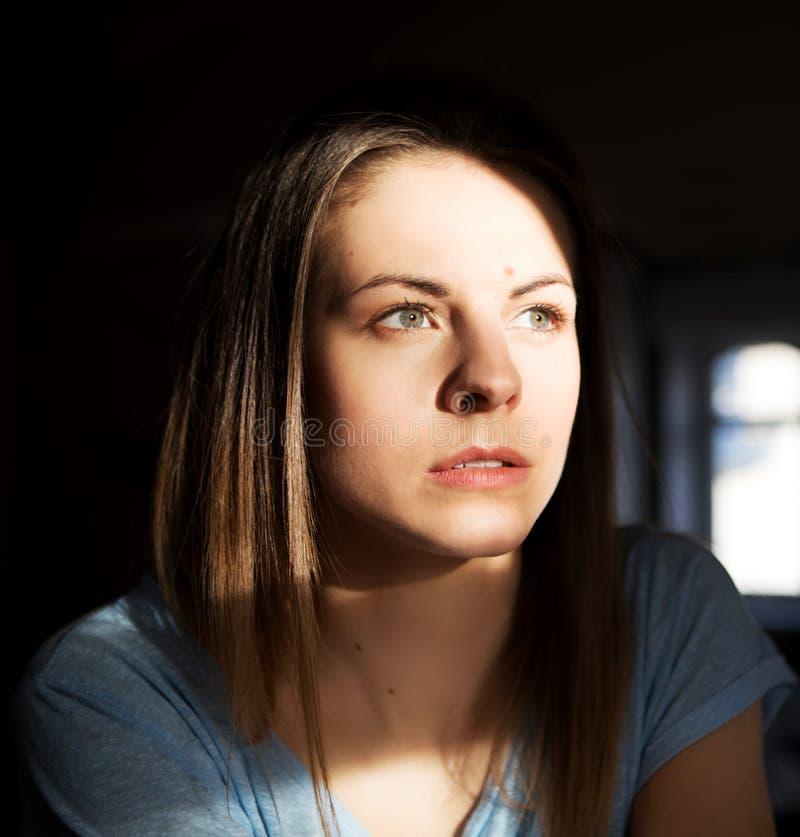 Портрет детенышей женщины задумчиво в доме стоковая фотография rf