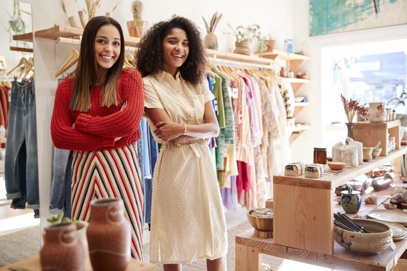 Портрет 2 женских ассистентов продаж работая в магазине одежды и подарка стоковые изображения
