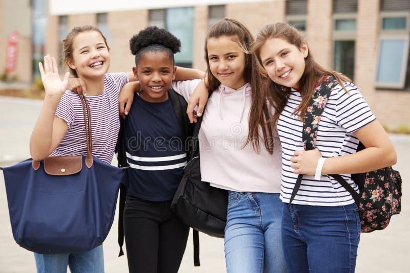 Портрет женских друзей студента средней школы стоя вне школьных зданий стоковая фотография rf