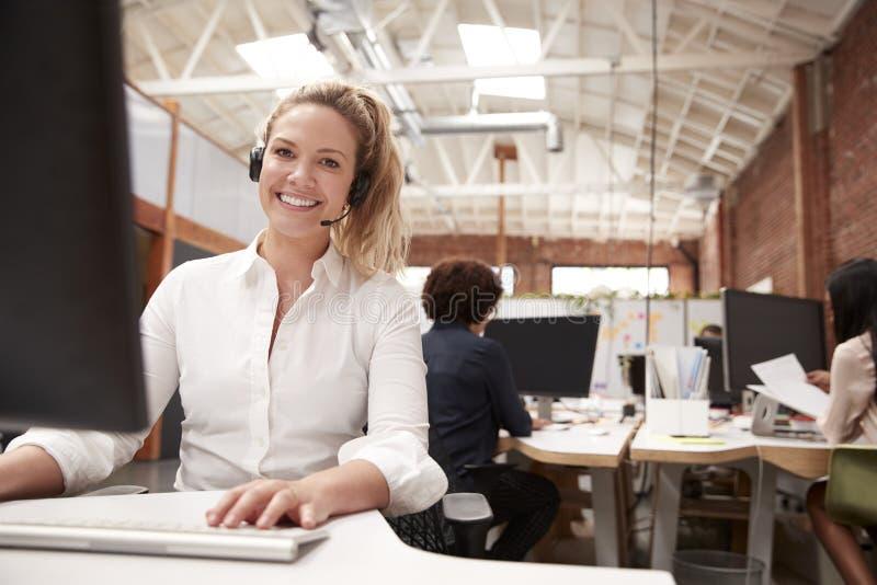 Портрет женского агента обслуживаний клиента работая на столе в центре телефонного обслуживания стоковая фотография rf
