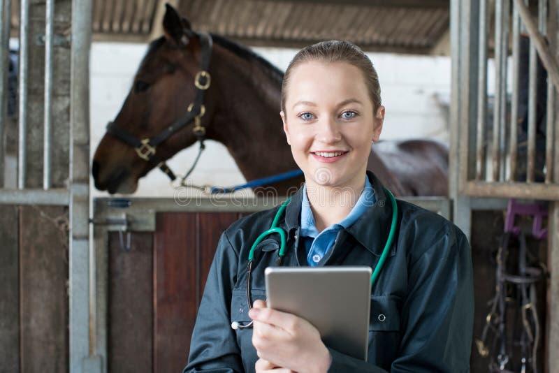 Портрет женского ветеринара с лошадью таблетки цифров рассматривая в St стоковые изображения
