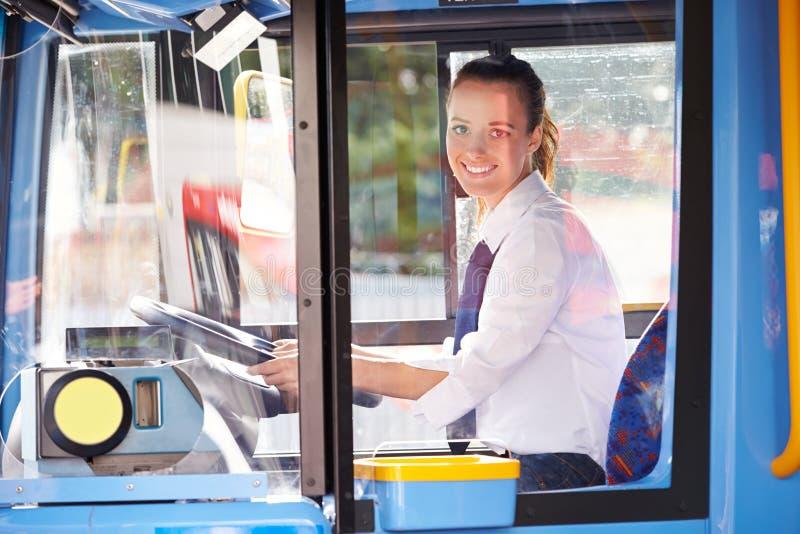 Портрет женского водителя автобуса за колесом стоковые фото