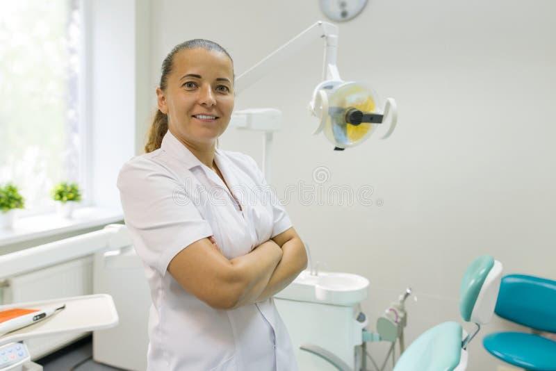 Портрет женского дантиста с пересеченными оружиями, доктором усмехаясь на зубоврачебной предпосылке стула Concep медицины, зубовр стоковое фото rf