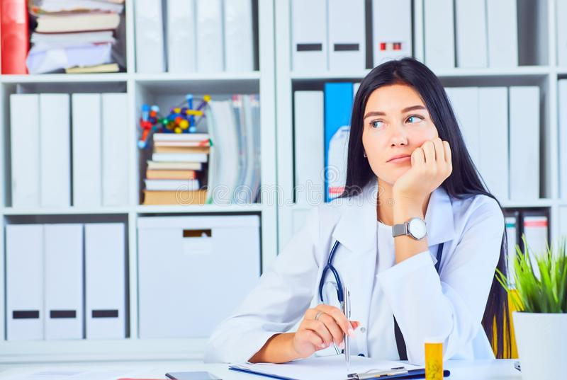 Портрет женского доктора therapeutist медицины сидя на ее офисе и ждать пациенте для того чтобы рассмотреть помогите медицинской стоковая фотография