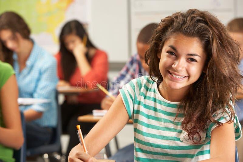 Портрет женского зрачка изучая на столе в классе стоковые фото