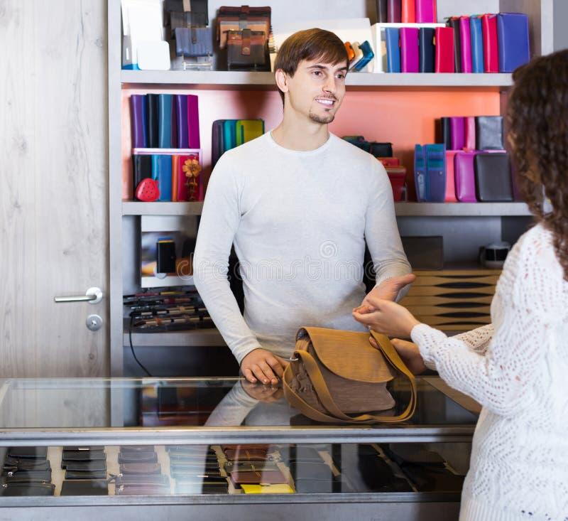 Портрет женского клиента и красивого парня продавая сумку стоковые изображения