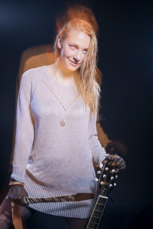 Портрет женского музыканта представляя с гитарой против черноты Используемые вспышка и галоид сочетания из стоковые изображения rf