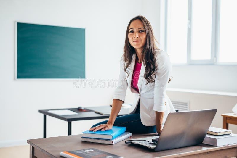 Портрет женского учителя коллежа усмехаясь на камере стоковое фото rf