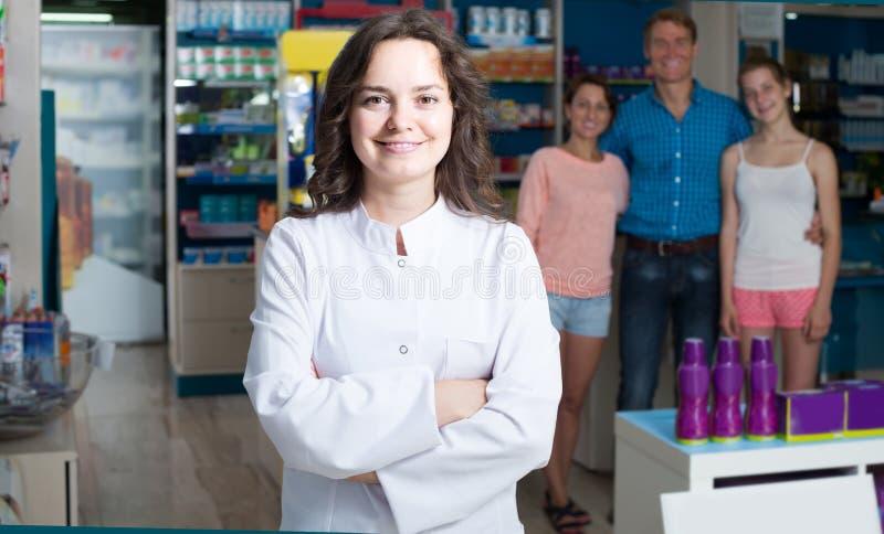 Портрет женского druggist в белом пальто работая в фармации стоковые изображения