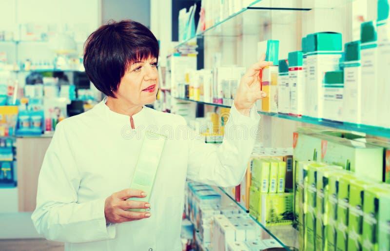 Портрет женского druggist работая в фармации стоковое изображение rf