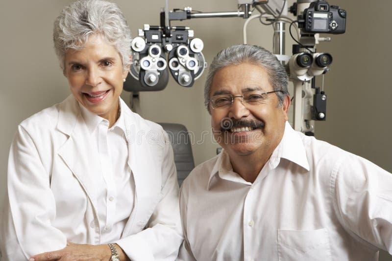 Портрет женского Optician с пациентом в хирургии стоковые изображения
