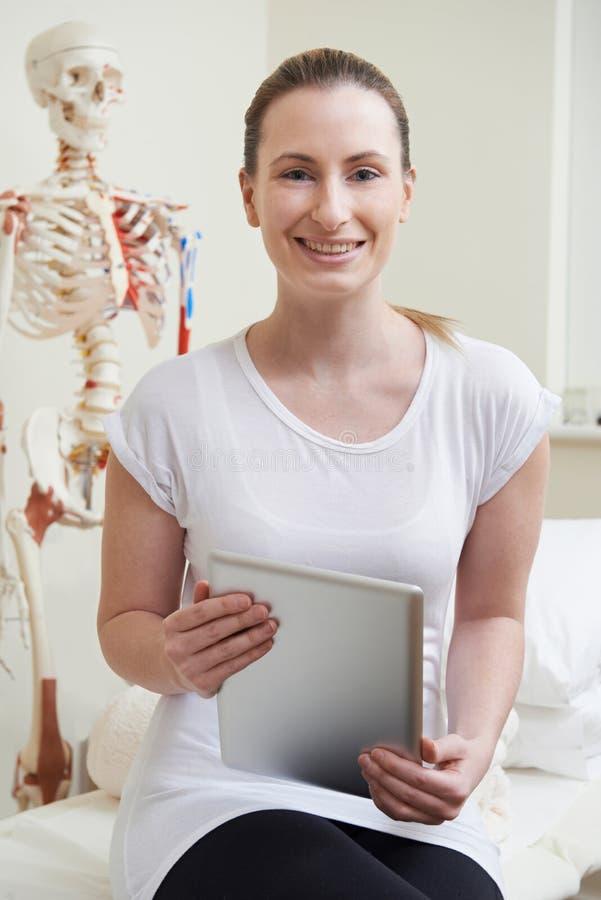 Портрет женского Osteopath в кабинете врача с платой цифров стоковые фотографии rf