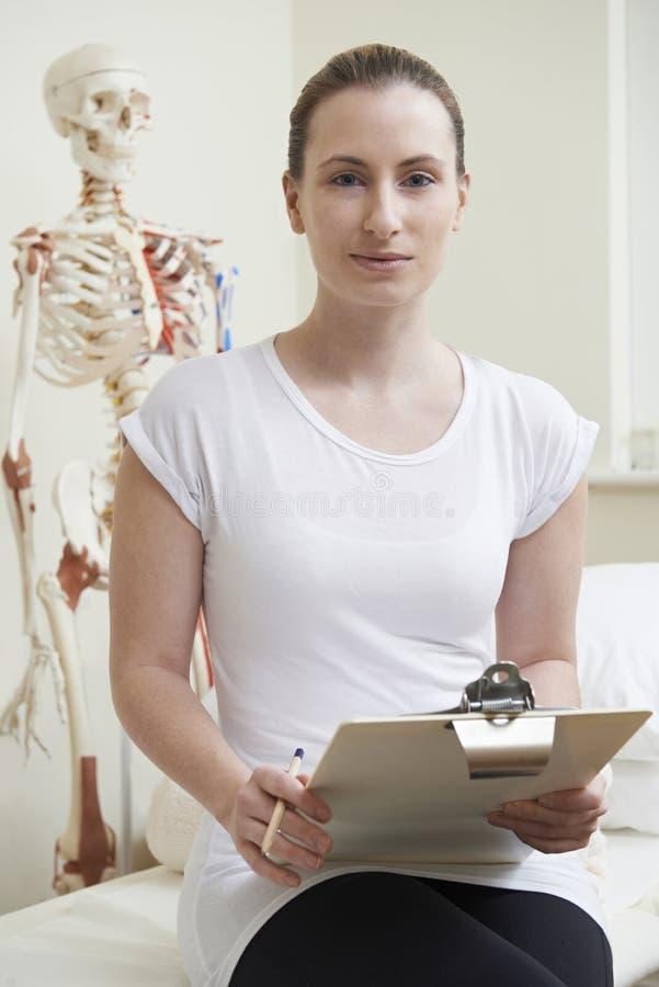 Портрет женского Osteopath в кабинете врача стоковые фото