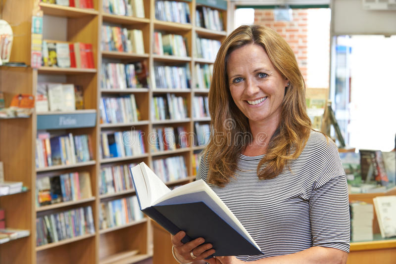 Портрет женской книги чтения клиента в Bookstore стоковое фото rf