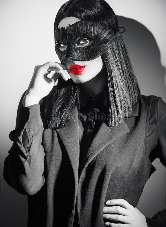 Портрет женщины брюнета красоты сексуальный Маска пера черноты масленицы девушки нося указывая рука, предлагая продукты стоковая фотография rf