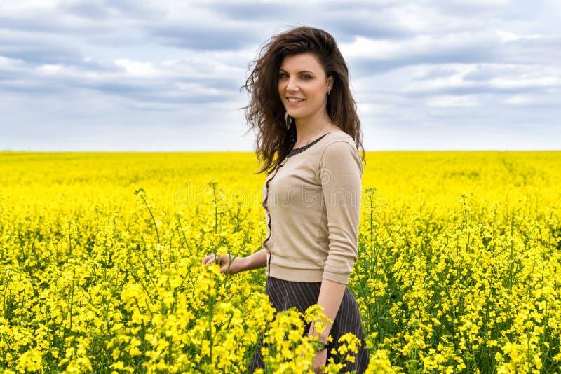 Портрет женщины в желтом поле цветка стоковые изображения