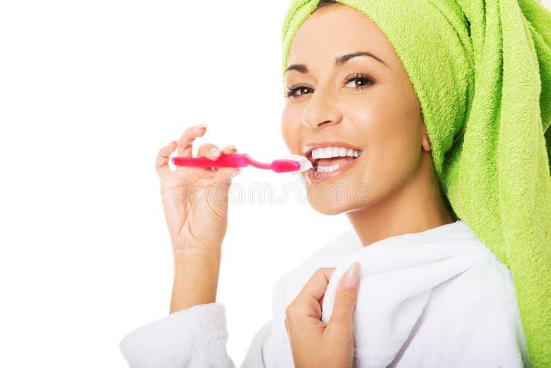 Портрет женщины в зубах купального халата чистя щеткой стоковая фотография