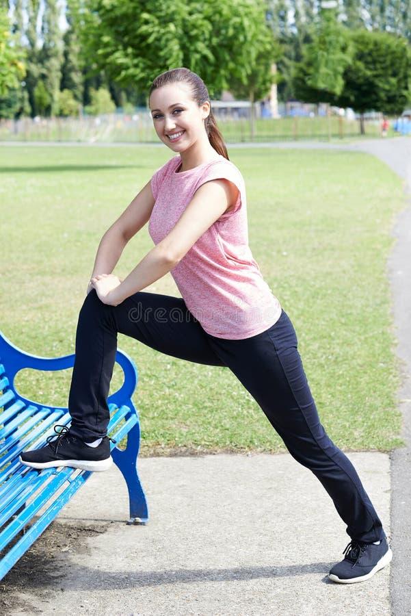 Портрет женщины в одежде фитнеса делая простирания используя парк стоковое фото rf