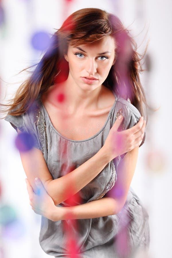Портрет женщины в платье стоя за занавесом стоковое фото rf