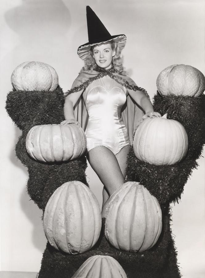 Портрет женщины в сексуальном костюме ведьмы окруженном тыквами на траве shelves стоковые изображения