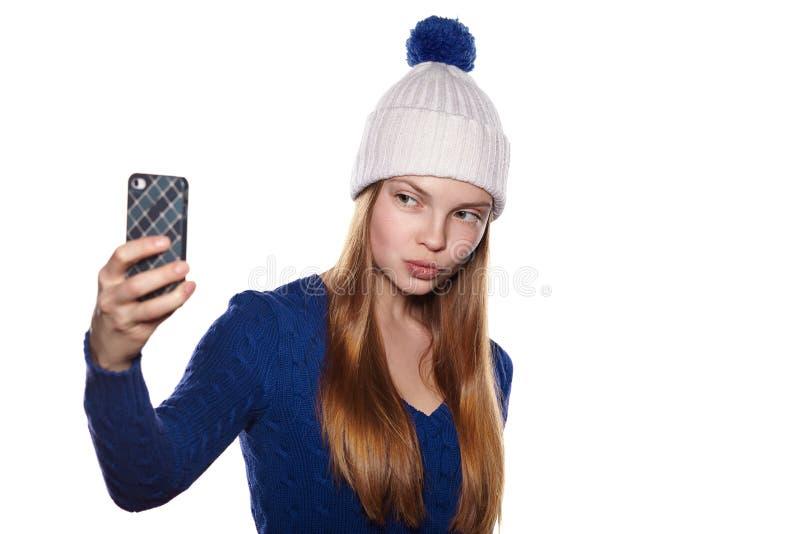 Портрет женщины в ткани зимы делая фото selfie стоковое изображение