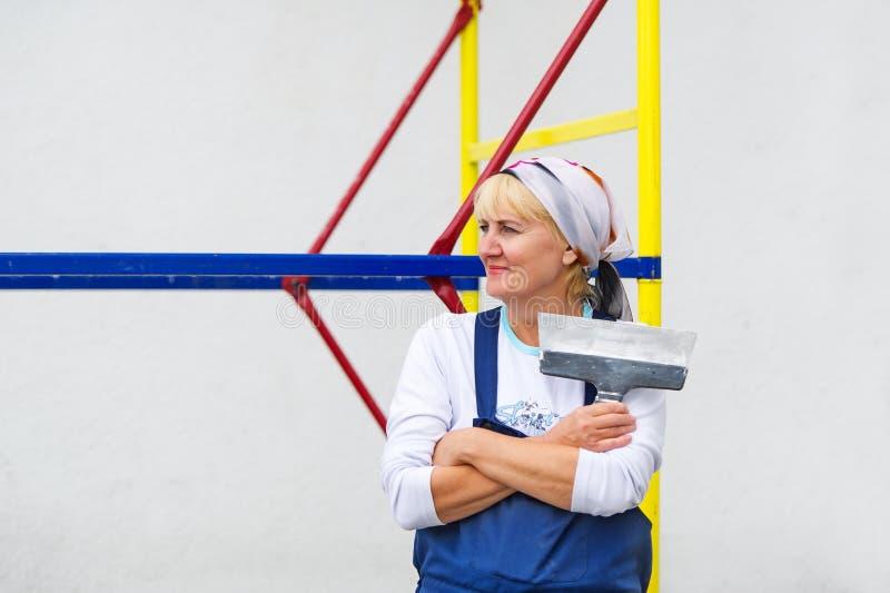 Портрет женщины в форме с шпателем в руках стоковые изображения rf