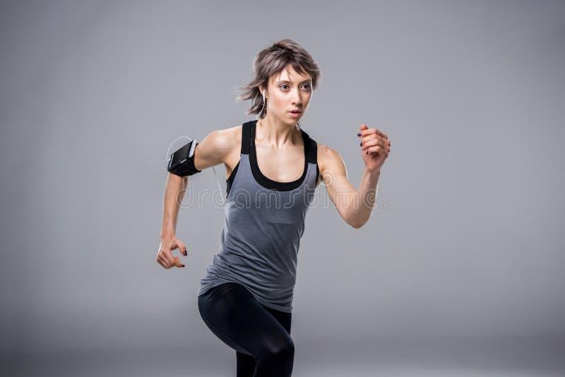 Портрет женщины в sportive одежде бежать в наушниках стоковые фотографии rf