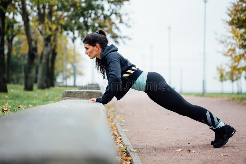 Портрет женщины в sportswear, делая фитнес нажим-поднимает тренировку на парке падения, внешнем стоковые изображения rf