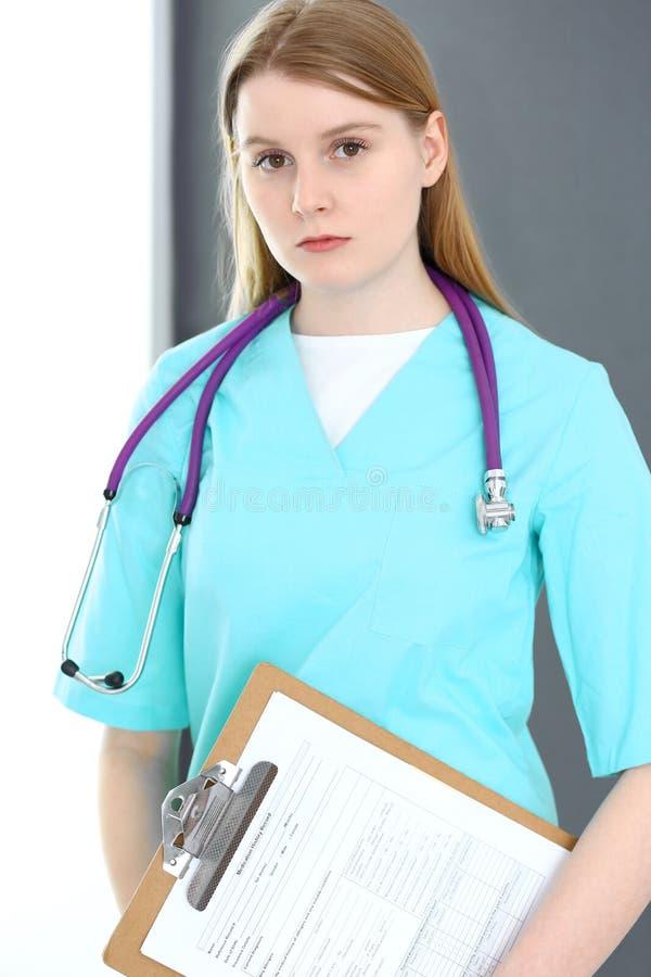 Портрет женщины доктора со стетоскопом Молодое женское положение хирурга или медсестры около серых стены и окна в клинике стоковое изображение