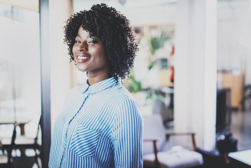 Портрет женщины детенышей довольно африканской при афро смотря и усмехаясь на камере Интерьер на предпосылке в современном стоковые изображения rf
