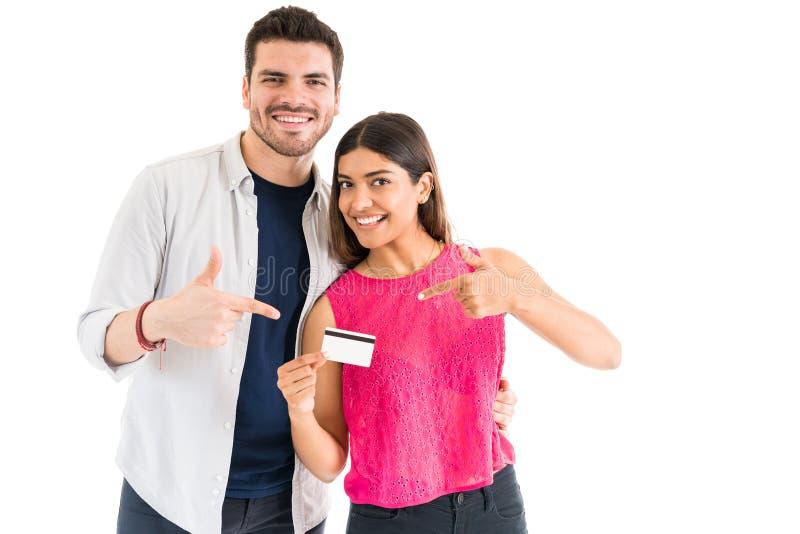 Портрет женщины и человека держа пластиковые деньги в студии стоковая фотография
