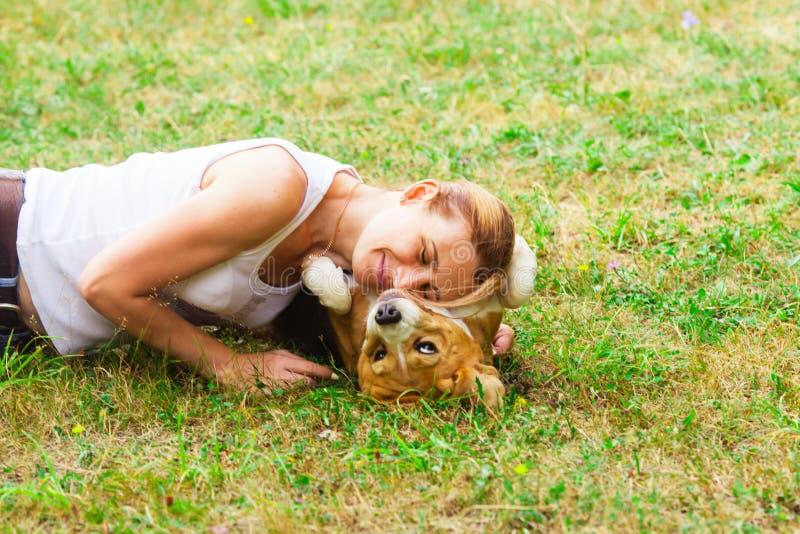Портрет женщины кладя ее сторону на собаку стоковое фото rf