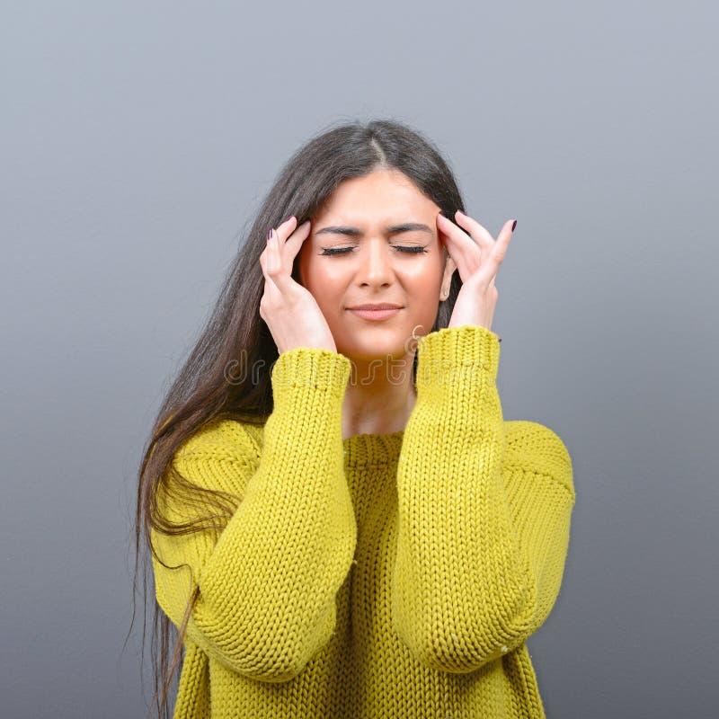 Портрет женщины концентрируя против серой предпосылки стоковое фото rf