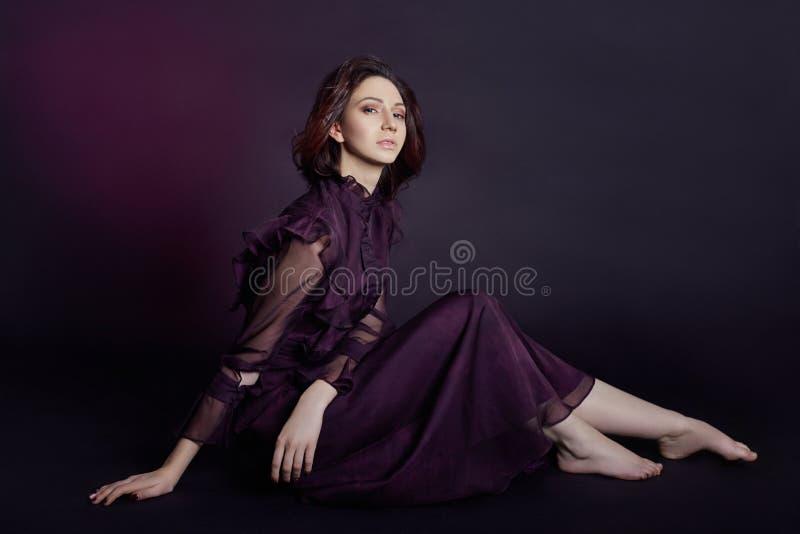 Портрет женщины моды контраста армянский с большими голубыми глазами сидит на темной предпосылке в фиолетовом платье Симпатичная  стоковая фотография