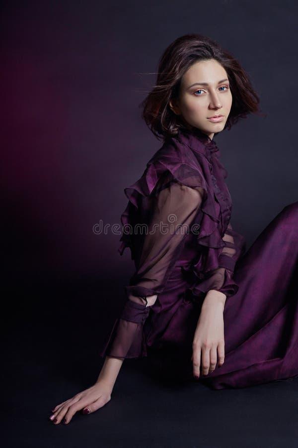 Портрет женщины моды контраста армянский с большими голубыми глазами сидит на темной предпосылке в фиолетовом платье Симпатичная  стоковая фотография rf