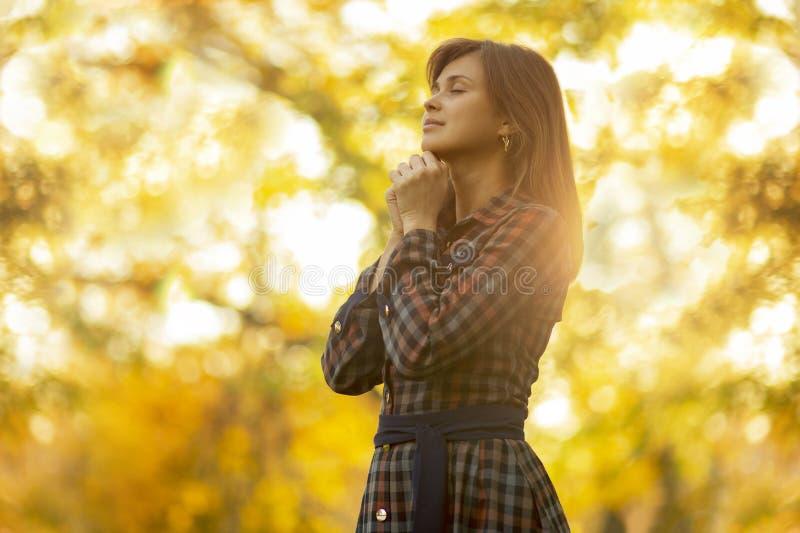 Портрет женщины моля в природе, бога спасибо девушки с ее руками сложенными на ее подбородке, разговором с Creato стоковое фото rf