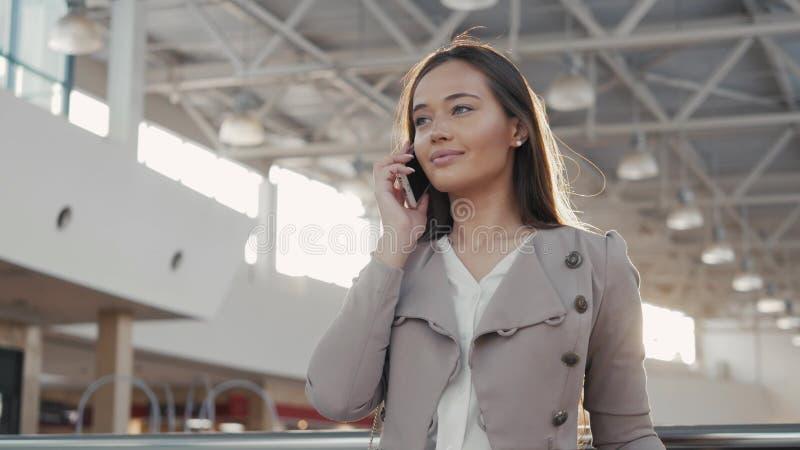 Портрет женщины молодого подростка туристской посещая покупки города используя ее прибор и усмехаться smartphone Бизнес стоковые изображения