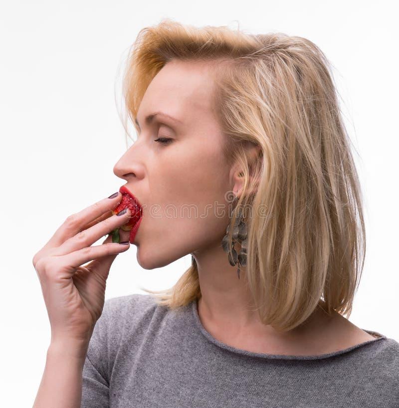 Портрет женщины наслаждаясь ел клубники стоковая фотография rf
