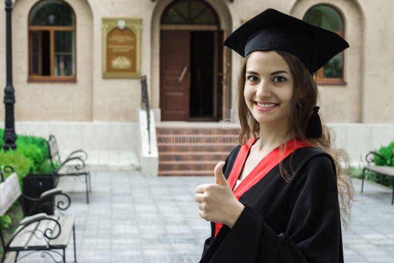 Портрет женщины на ее выпускном дне большие пальцы руки вверх университет Образование, градация и концепция людей стоковое фото