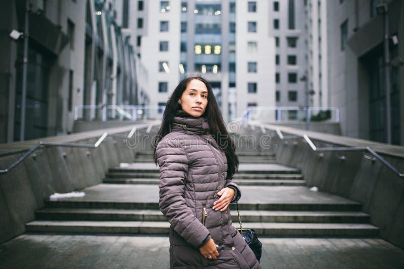 Портрет женщины на теме дела Молодая кавказская девушка брюнет в длинной куртке, пальто с черной кожаной сумкой стоит на busin стоковое изображение