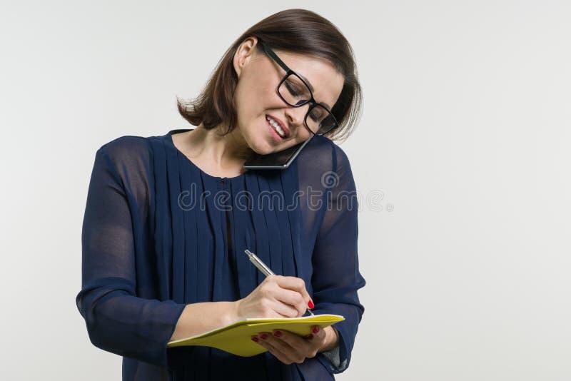 Портрет женщины пишет на тетради и телефон вызывать стоковая фотография