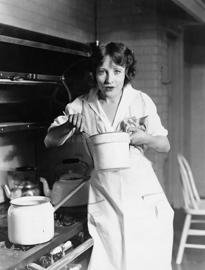 Портрет женщины подготавливая еду в кухне (все показанные люди более длинные живущие и никакое имущество не существует Warr поста стоковые фотографии rf