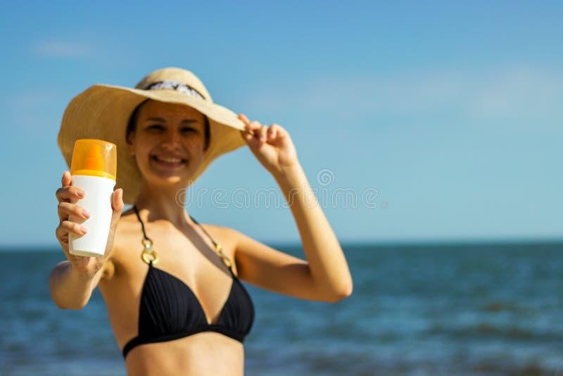 Портрет женщины принимая skincare с лосьоном солнцезащитного крема на пляж стоковое изображение