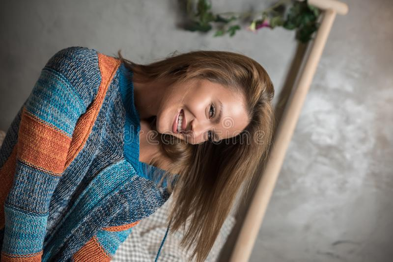 Портрет женщины сидя на кровати и нося свитер стоковые фото