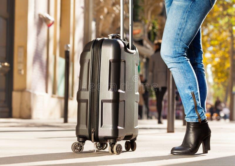 Портрет женщины стоя на улице с чемоданом стоковые фотографии rf