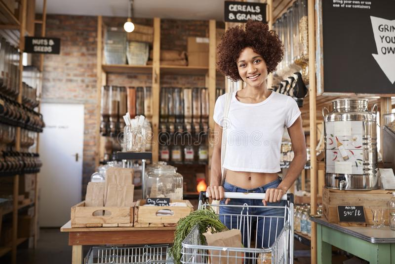 Портрет женщины с вагонеткой покупок покупая свежие овощи в пластиковом свободном гастрономе стоковая фотография rf
